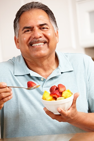 Man eating fresh fruit from a bowl.