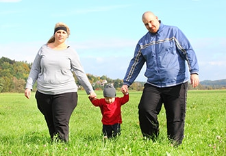 Overweight family walking together outdoors.