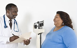 Doctor In Lab Coat Weighing Obese Patient Blue Shirt Talk With Your About Which Weight Loss Medication