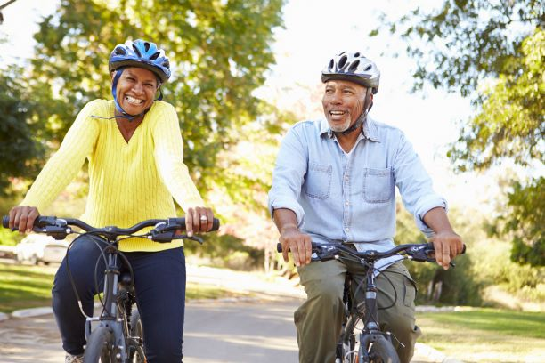 An older couple biking in the countryside, wearing helmets.