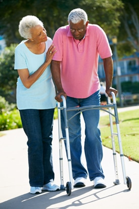 Woman helping man walk with a walker