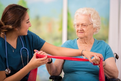 Older woman in a wheelchair working with resistance bands with help from a health care professional.