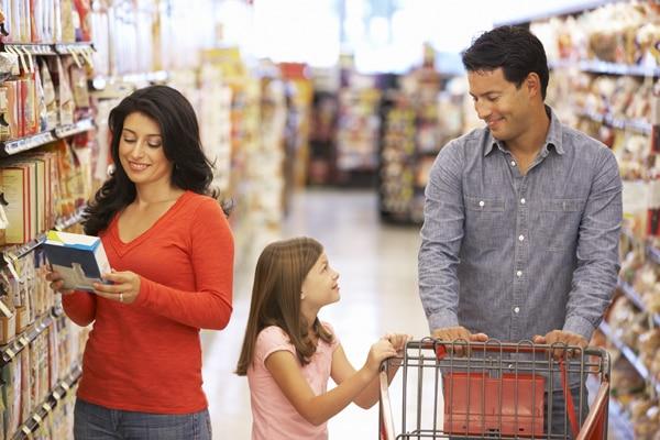 Una mujer que está leyendo los envases de los alimentos en un supermercado con su familia.
