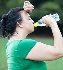 A woman drinking water after sweating from exercising