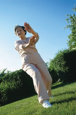 Older woman doing tai chi outside.