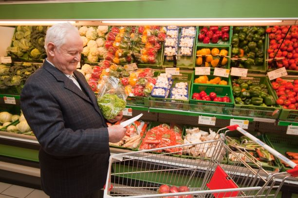 An older man shopping in a supermarket's produce aisle.
