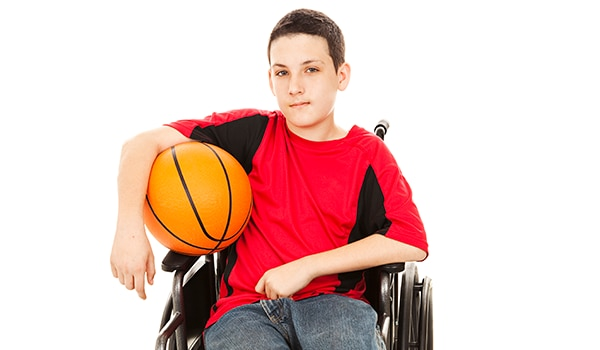 Teen in a wheelchair with a basketball