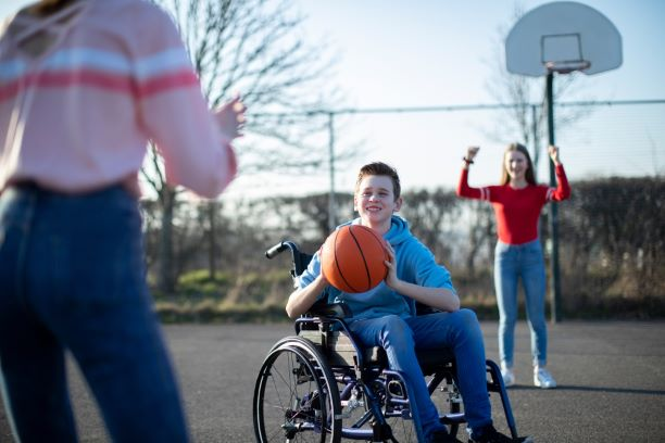 A teenage boy in a wheelchair plays basketball with friends.