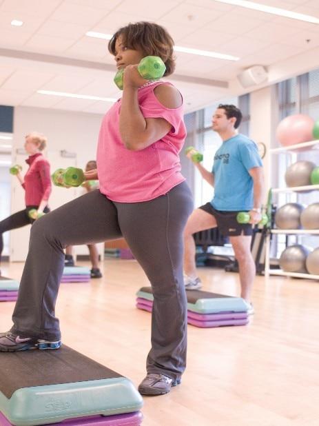 Uma mulher levantando pesos em uma aula de ginástica