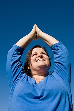 Woman with her arms raised over her head in a yoga pose.