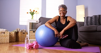 Woman sitting on a yoga mat on her living room floor, leaning on a balance ball, with a pair of weights and water bottle next to her.
