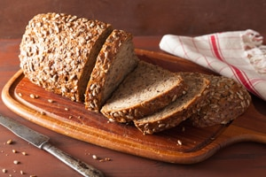 Photo of  sliced loaf of whole grain bread on a cutting board