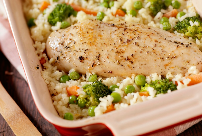 Baking dish with roasted chicken, peas, carrots, and rice.