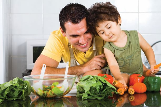 Father and his young son prepare a salad with bell peppers, carrots, and lettuce.