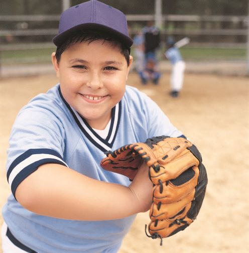 A smiling boy in a baseball uniform holds a ball and baseball glove.