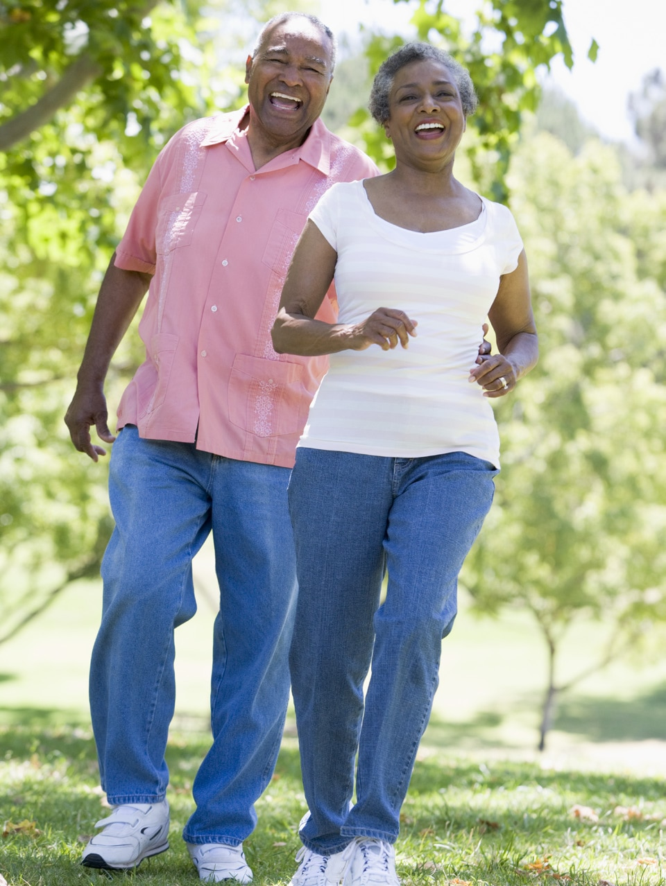 Elderly couple walking together through the park.
