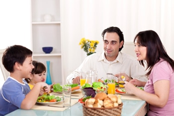 Photo of two adults and two children sharing a meal around a dinner table