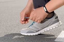 A person tying their running shoes while wearing a fitness tracker band