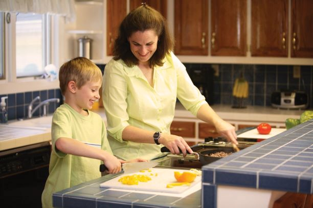 Mother and school-age son prepare a meal in their kitchen.
