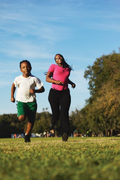 A mother and son run side by side on a grassy field.