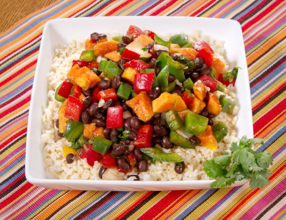 Dish of cooked black beans with bell peppers and brown rice.