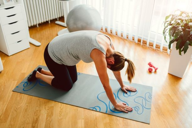 Pregnant woman does yoga pose on a yoga mat.