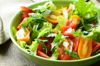 Photo of a fresh green salad with tomatoes in a bowl