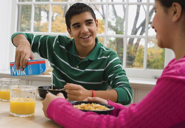 Teen boy and his mother eat a breakfast of whole-grain cereal, low-fat milk, and fresh fruit juice.