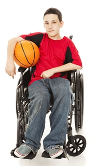 Photo of  boy sitting in wheelchair holding basketball