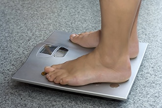 Patient standing on weight scale.