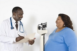 Health Care Professional Talking With Woman Standing On A Scale.