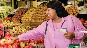 A woman choosing produce at the grocery store.
