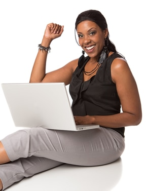 Woman holding a laptop and sitting on the floor with outstretched legs