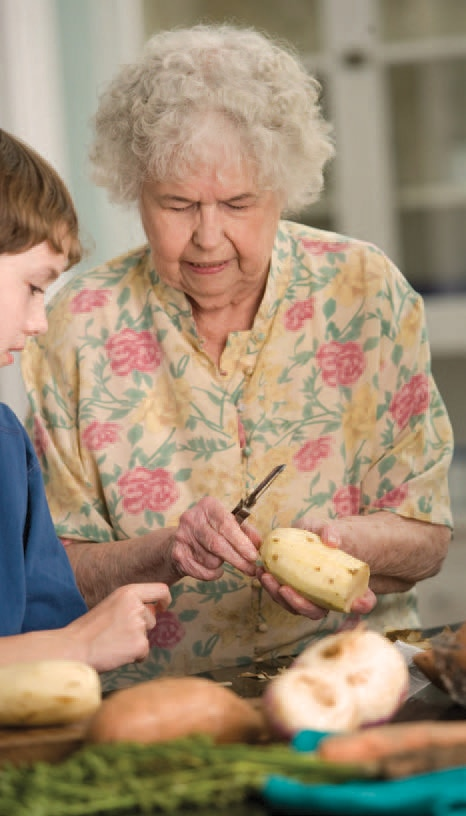 An older woman and a boy prepare food together.