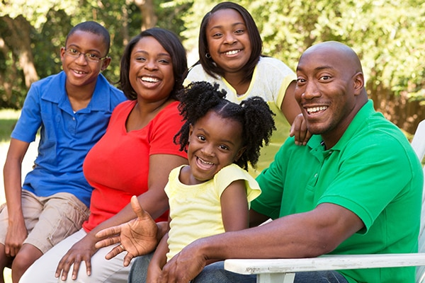 An African American family sitting and smiling.