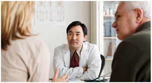 An image of a male health professional speaking with older male and female patients