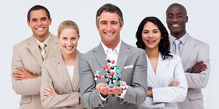 Five professionals with one holding a model of a molecule