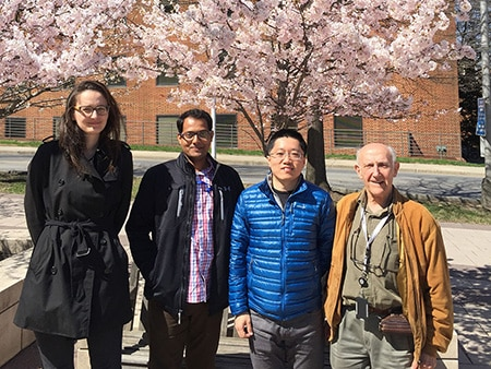 Photo of lab members in front of cherry blossom tree
