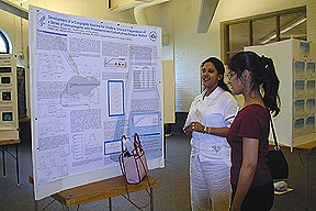 Photo of Rina Saksena explaining her poster at the 2003 Gordon Research Conference