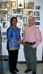 Photo of Rina and Paul in front of a wall with photos of past lab members