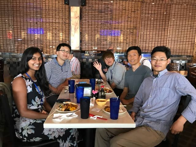 Members of the lab eat lunch around a table.