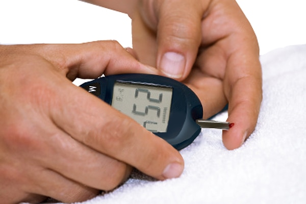 Photograph of two hands holding a blood glucose meter. A test strip extends from the meter to one index finger. A drop of blood has been applied to the end of the test strip. The screen on the meter that shows results says 254.