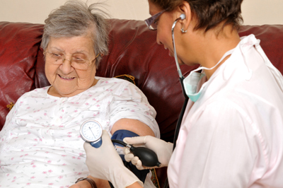 A woman having her blood pressure checked by a health care professional.