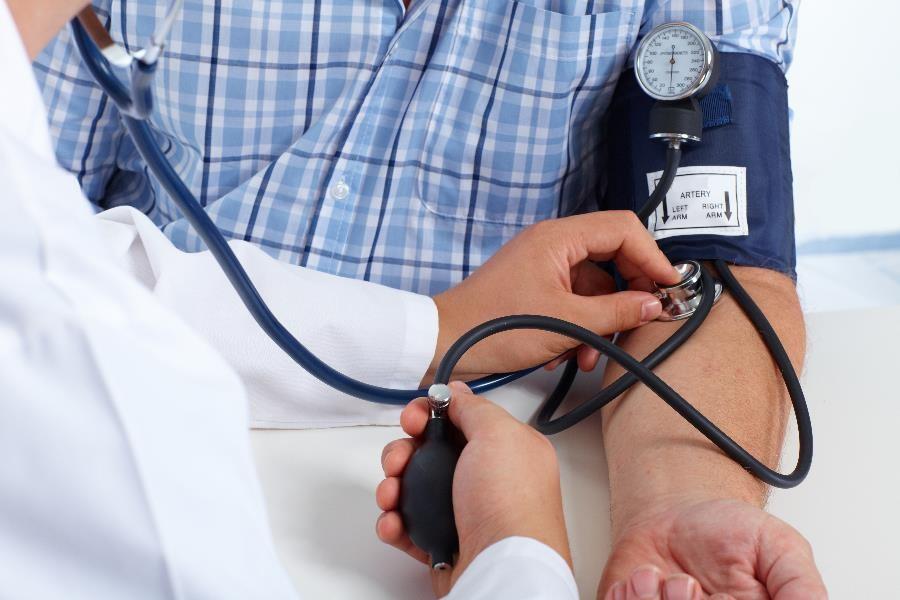 Foto que muestra un acercamiento de un médico evaluando la presión arterial de un paciente.