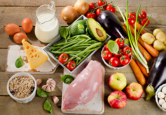 A variety of healthy, nutritious foods including vegetables, fruits, whole grains, cheese, eggs, milk, and chicken.