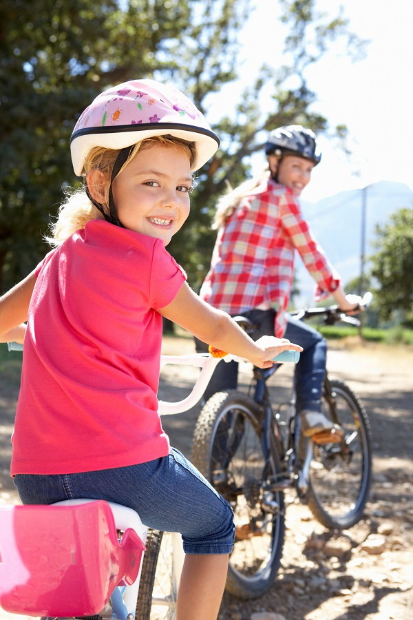 Photo of mother and young daughter riding bikes