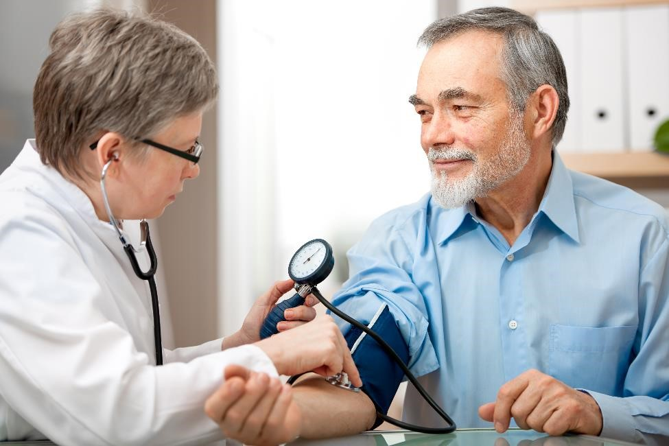 A health care professional measures the blood pressure of an older patient using a blood pressure cuff.