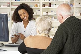 Una pareja hablando con un farmacéutico.
