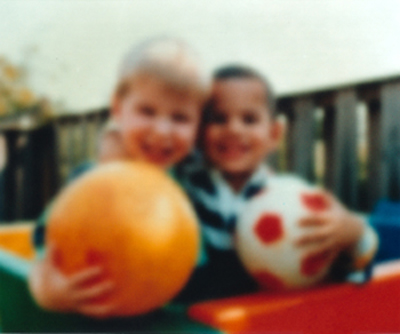 A blurry photo shows two boys with rubber balls. The photo shows how cloudy lenses in the eye, called cataracts, affect vision.