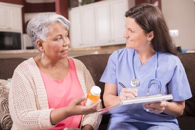 Foto de un médico hablando de medicinas con un paciente anciano.